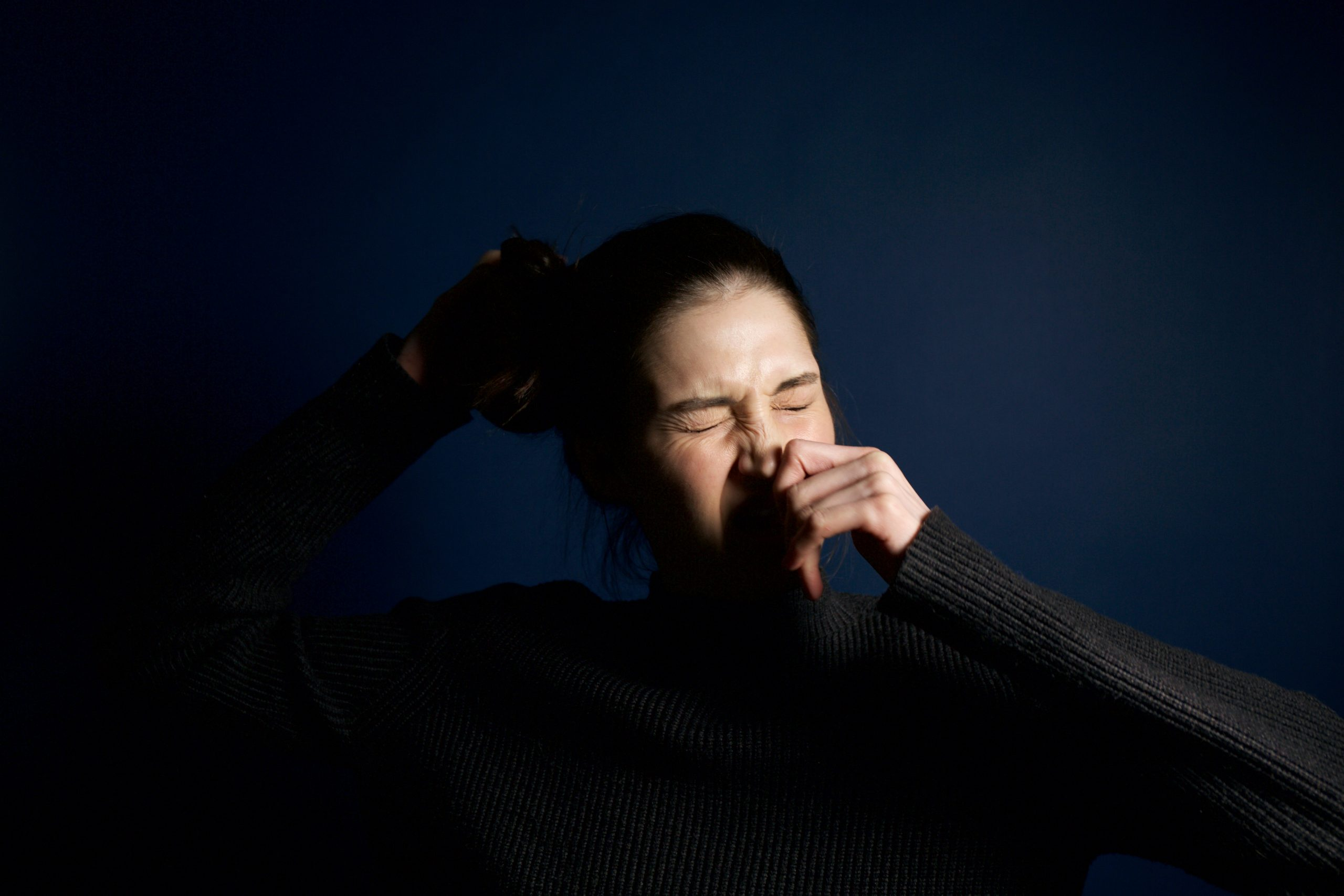 Woman sneezing; allergies, a cold, or the flu.