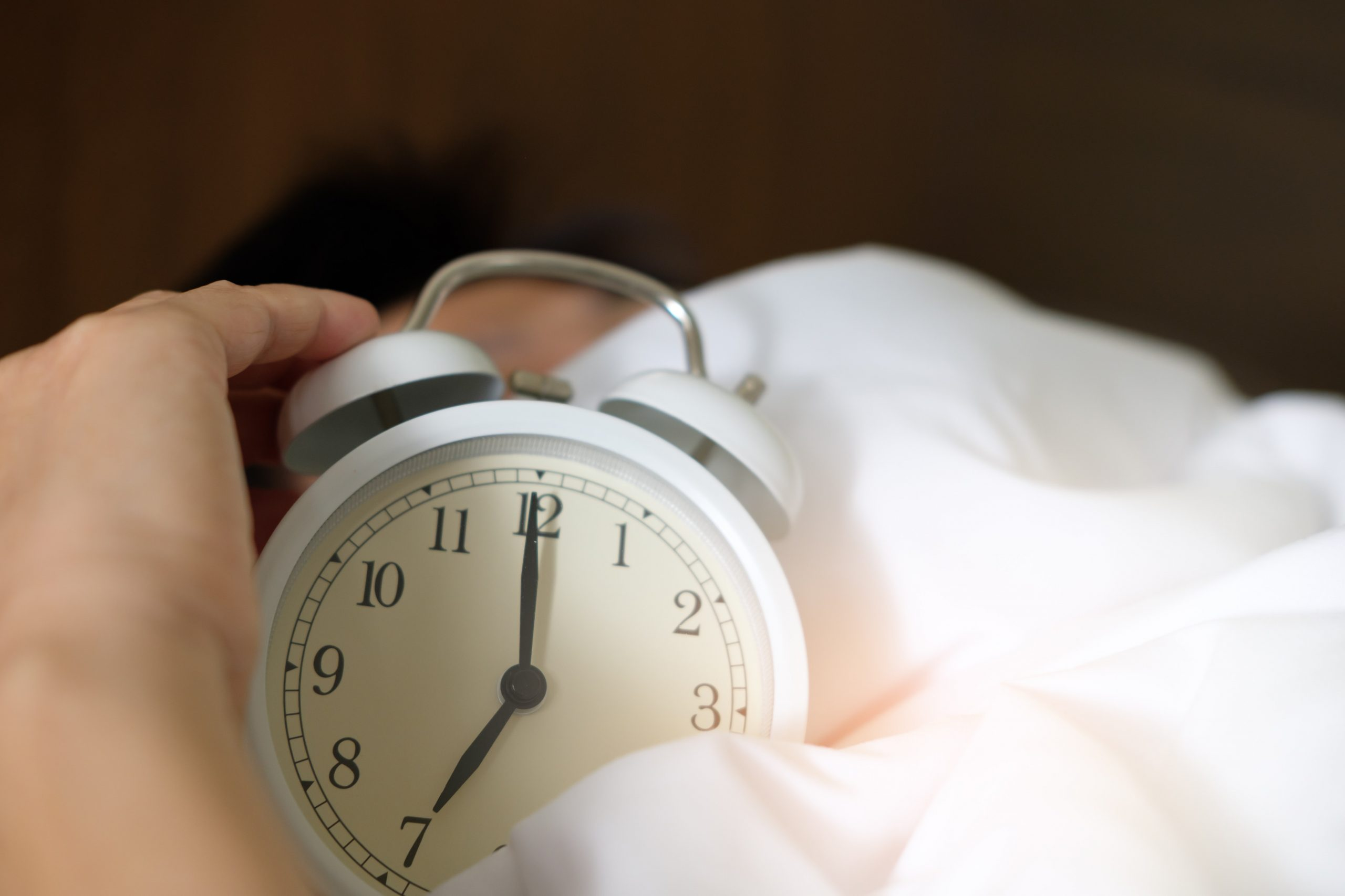 Person holding alarm clock; insomnia causes and solutions.