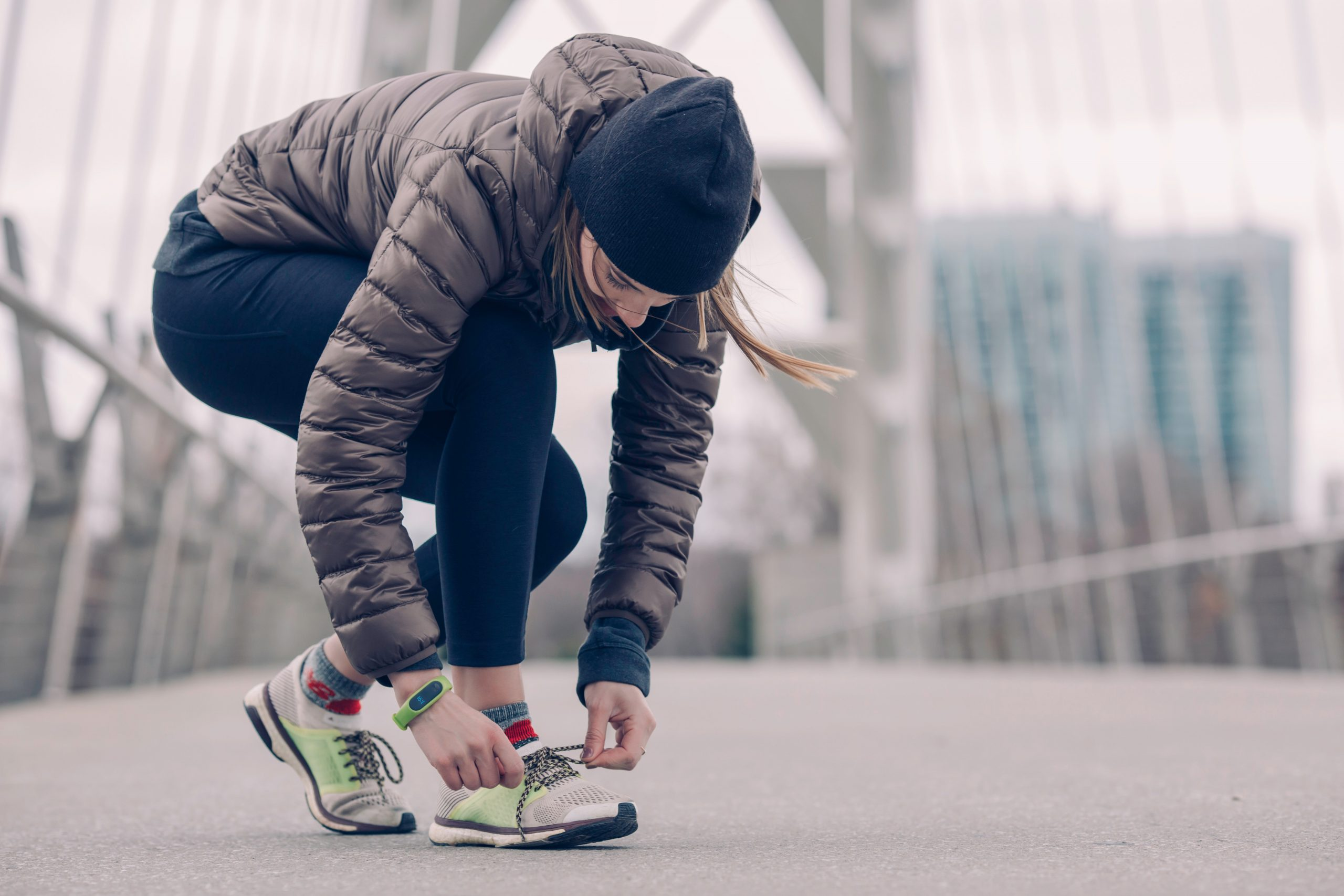 Woman tying shoe to exercise; tips for healthy weight management.